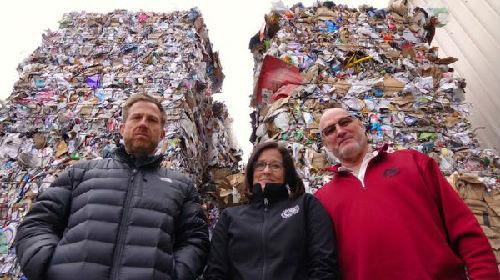 """中国的""""禁废令""""让美国的垃圾供过于求。图为俄勒冈一个回收公司的员工站在堆积如山的垃圾前。(美国全国公共广播电台网站)"""