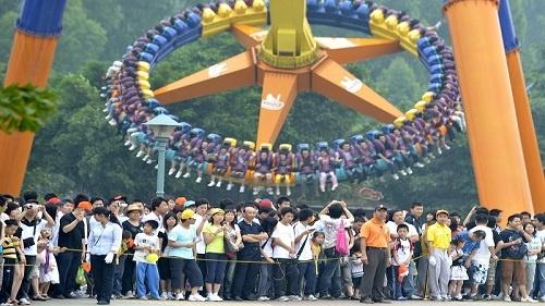 2018年5月1日,在广州长隆欢乐世界景区内,游客排起长队等待游乐项目。新华社记者 刘大伟 摄