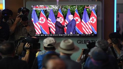 12日,韩国民众在首尔火车站的屏幕前观看美朝领导人会晤直播。(法新社)