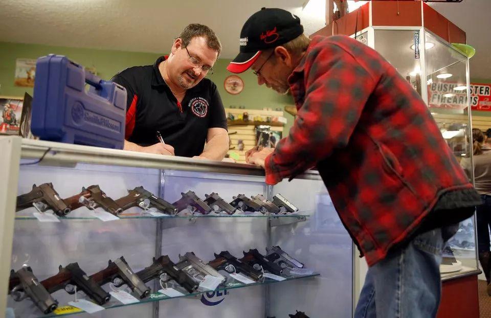 ▲美国密苏里州的一家枪支店内,一名顾客正在买一把手枪。(美联社)