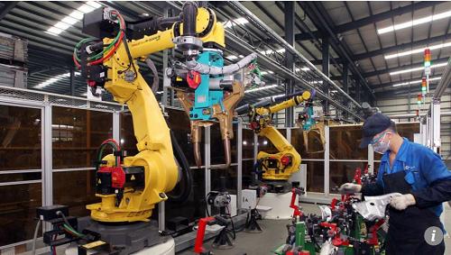 在江苏昆山的一家汽车配件厂,工业机器人正在加工汽车配件。(香港《南华早报》网站)