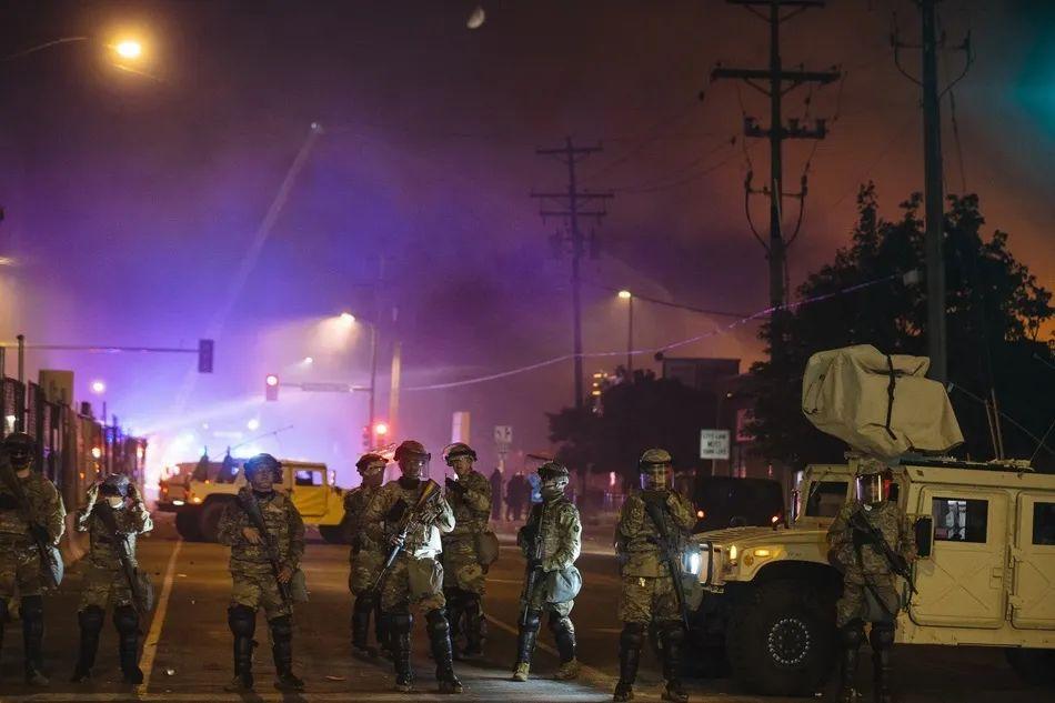 美国明尼苏达州明尼阿波利斯市,国民警卫队成员在一处起火建筑附近警戒