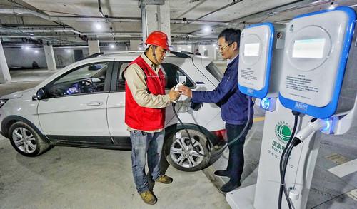 资料图片:国网北京电力公司的技术人员在为新能源汽车进行试验充电(2017年10月27日摄)。新华社记者 李欣 摄