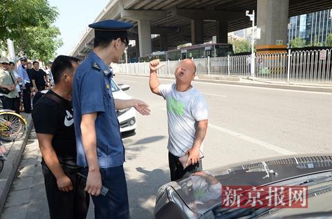 一名涉嫌驾驶车辆逆行以及非法载客的司机向执法人员辩解。