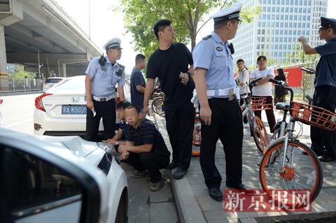 执法人员控制两名名涉嫌非法载客的司机。新京报记者 吴江 摄