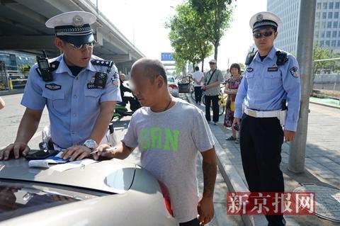 一名涉嫌驾驶车辆逆行以及非法载客的司机在处罚单上签字。