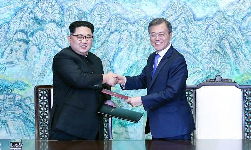 2018年4月27日,朝鲜国务委员会委员长金正恩(左)与韩国总统文在寅在板门店交换签署的《为实现半岛和平、繁荣和统一的板门店宣言》(简称《板门店宣言》)。新华社发