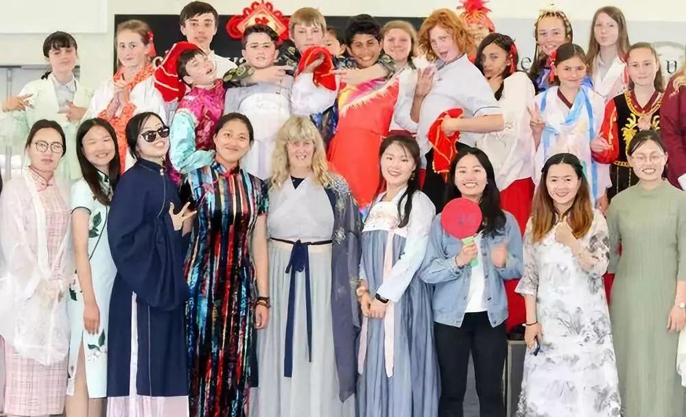"""11月19日,在新西兰罗托鲁阿初级中学,中文助教乔巾哲(前排左四)、该学校老师安·希恩(前排左五)等人在""""发现中国文化""""活动结束后合影。新华社发"""