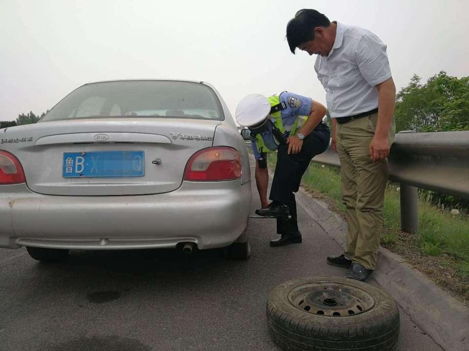 烈日下的守护者:轿车轮胎被扎破 交警热心来帮忙