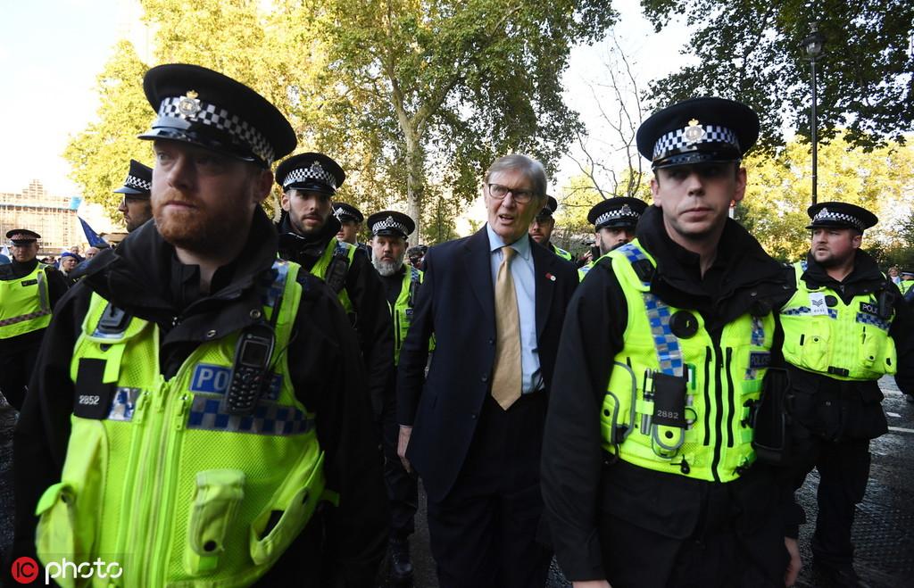 10月19日,英国伦敦,议员比尔卡什在警方护送下离开议会大厦。图自IC Photo