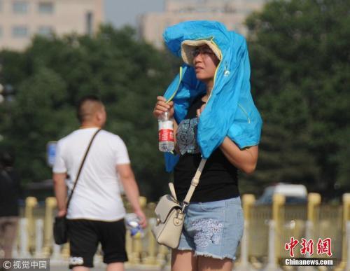 资料图:5月31日,北京骄阳似火、热浪滚滚,游客顶烈日游览。杜桂 摄 图片来源:视觉中国