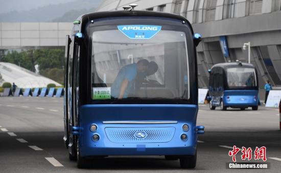 """4月22日,无人驾驶巴士""""阿波龙""""载着乘客行驶在路面上。中新社记者 张斌 摄"""