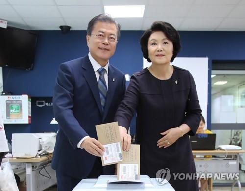6月8日,在首尔三清洞居民中心,韩国总统文在寅(左)和夫人金正淑进行地方选举缺席投票。(图片来源:韩联社)