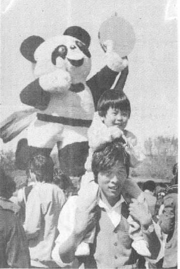 """1990年,旅客争相取天安门广场的""""盼盼""""外型花坛开影。 胡敦志/摄"""