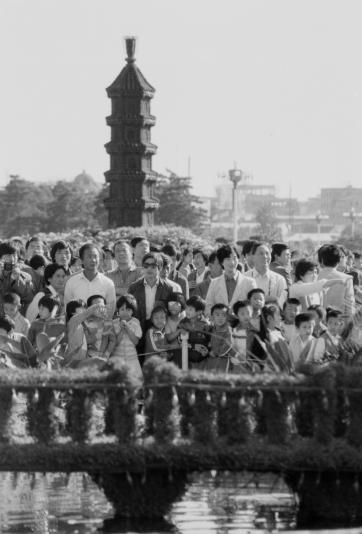 """人们站正在天安门广场的""""延安浮图""""下留影。胡敦志/摄"""