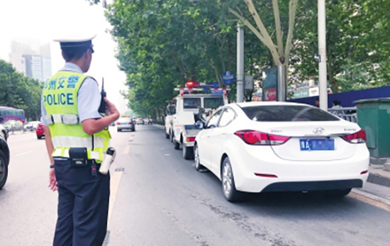 主干道上乱停车且找不到车主者,交警将车拖离现场。大河报 图