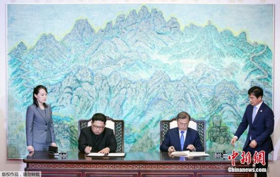 当地时间4月27日下午,韩朝领导人在经过一天会谈后签署协议,共同签署《板门店宣言》,并在和平之家外举行发布会。图为签署仪式现场。