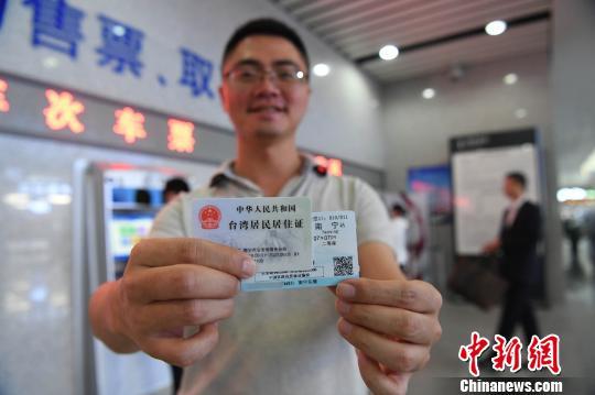 周代祥展示用居住证在购票机上买到的动车票。 俞靖 摄