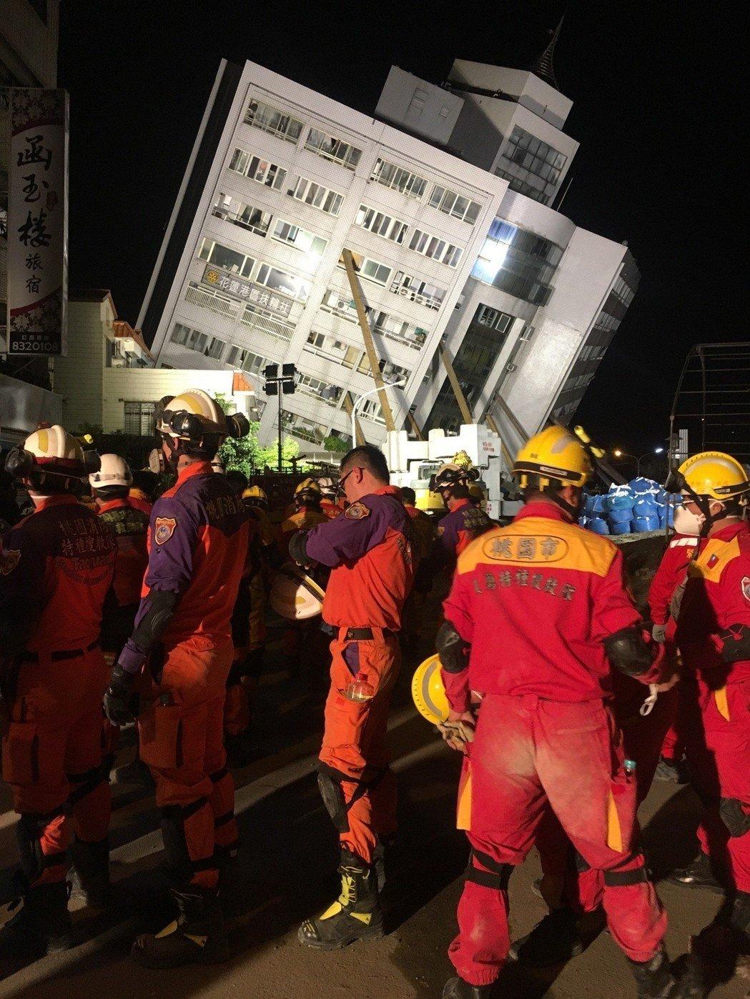 """大批台湾搜救人员步出受灾大楼,身上满是灰尘(图片来源:""""联合新闻网"""")"""