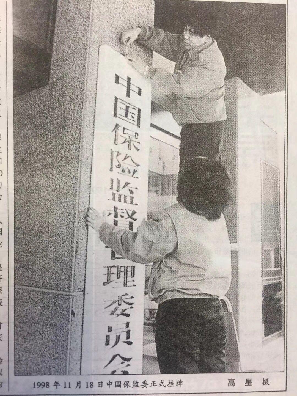 """▲图为1998年11月18日保监会成立大会召开后的""""挂牌"""",据照片拍摄者高星表示,当时没有挂牌仪式,正在挂牌子的是保监会办公室两位行政人员。图片刊发于1999年第1期《中国保险》杂志。"""