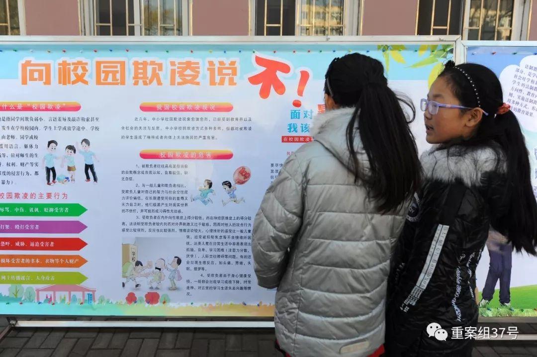 """2017年11月23日,青岛广饶路小学的学生在操场上学习""""向校园欺凌说不""""法制教育宣传图版。图片据视觉中国"""