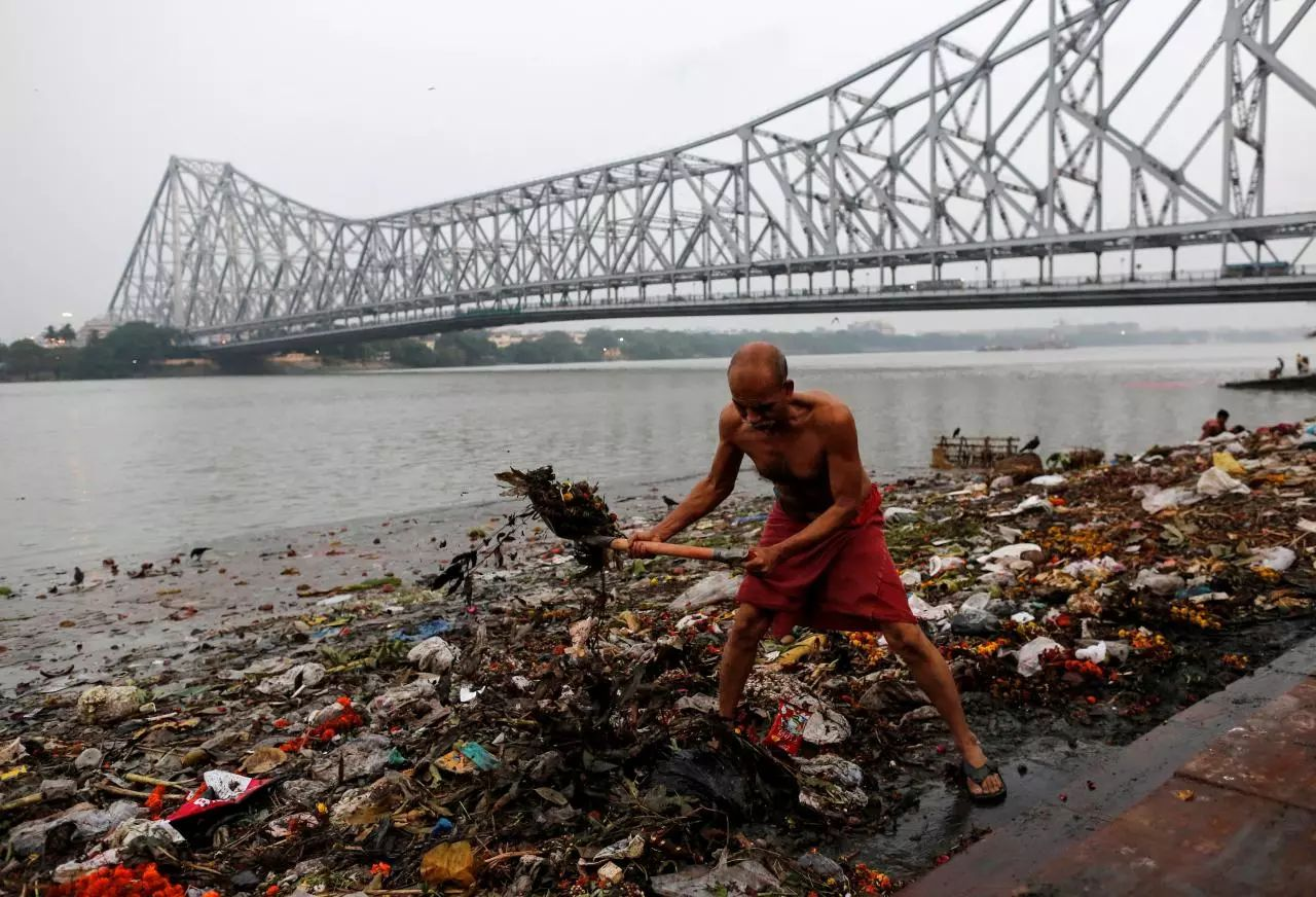 ▲一名男子在恒河旁处理岸边的垃圾。(路透社)