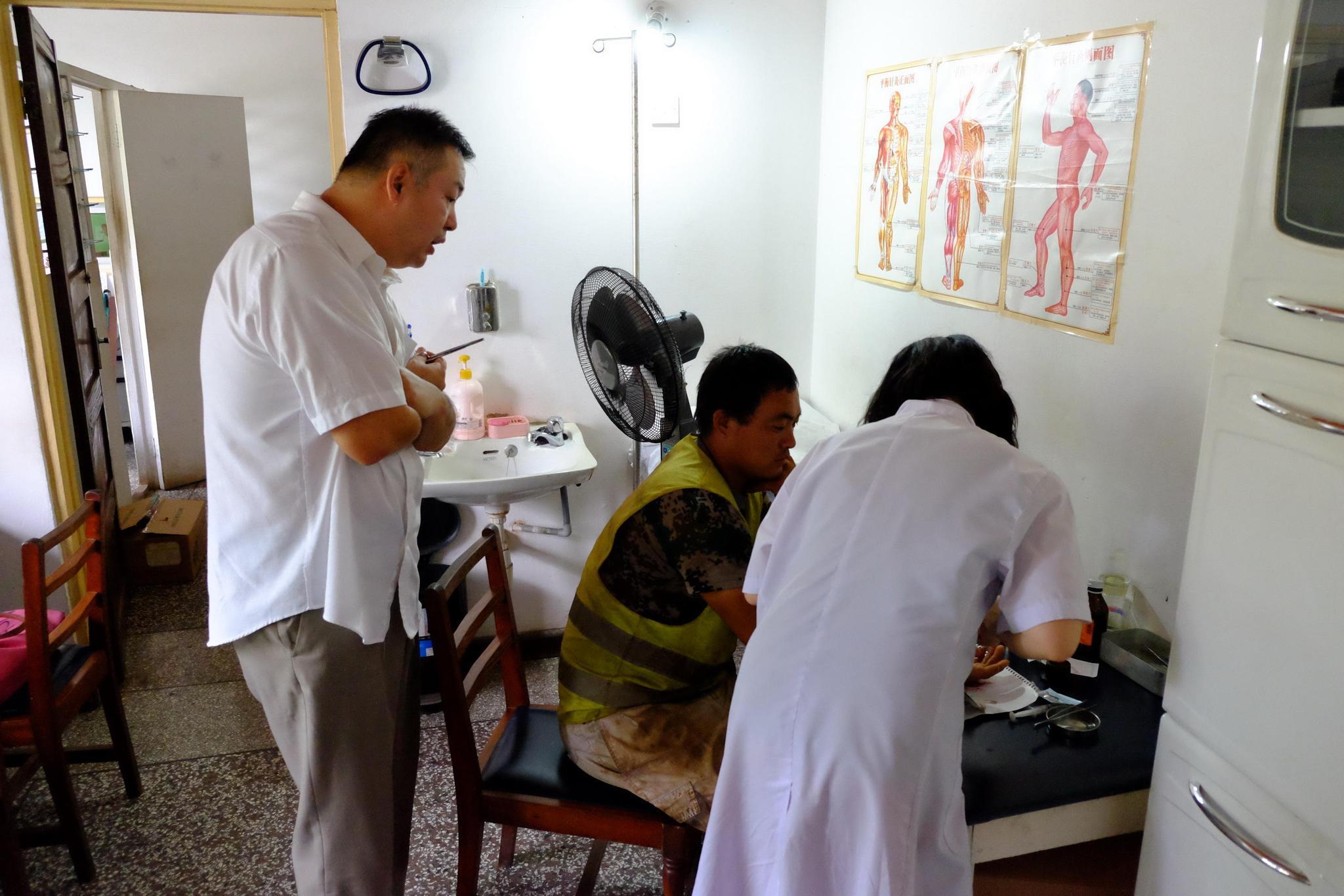 11月21日,萧可佳(左一)与另一名医生曹珂为手指受伤的患者处理伤口。