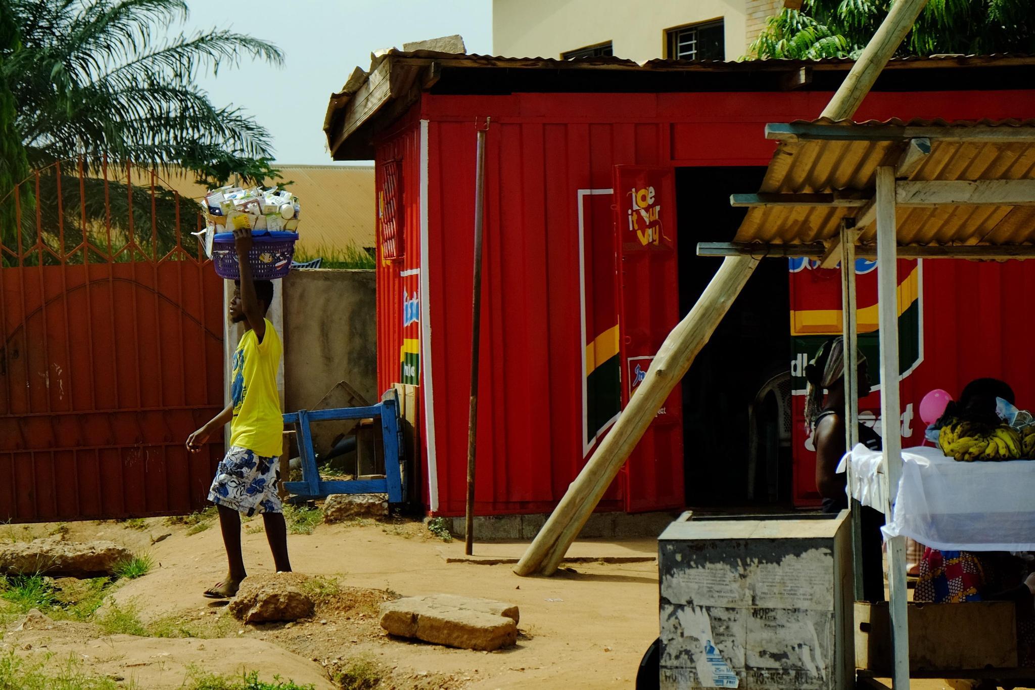 11月28日,加纳首都阿克拉街头,一个顶着东西走过的路人。