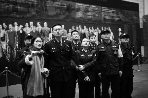 现代快报记者徐红艳(左)为参观的警官介绍油画创作背后的故事