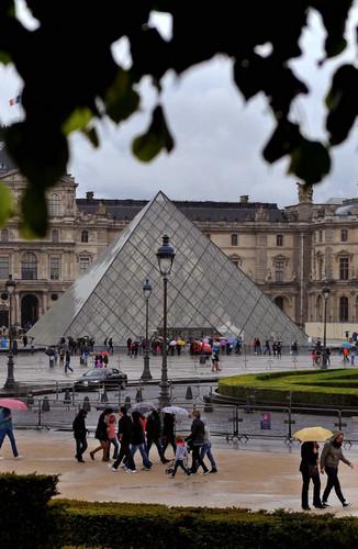 资料图片:2014年5月1日,游客冒雨在巴黎卢浮宫参观。新华社记者 陈晓伟 摄