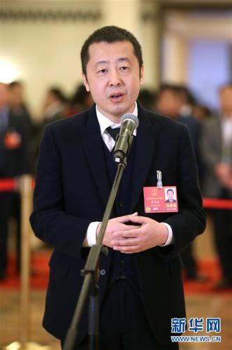 """3月11日,十三届天下人年夜一次集会在北京国民年夜礼堂举办第三次全部集会。这是天下人年夜代表贾樟柯在""""代表通道""""接收采访。新华社记者 金破旺 摄"""