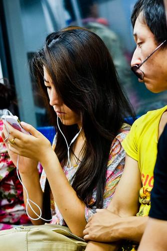 资料图片:2012年7月18日,在北京地铁二号线列车上,一名年轻人在玩手机游戏。新华社发