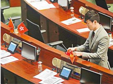 郑松泰把议员座席上的国旗和香港特区区旗倒转(图源:香港文汇网)