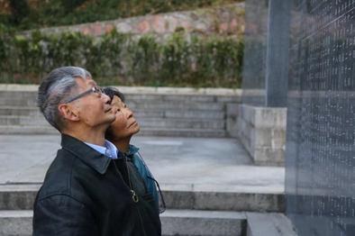 """▲12月5日,鲁照宁的怙恃在抗日航空义士纪念馆的英烈墙上寻找""""鲁美音""""的姓名。南京抗日航空义士纪念馆供图"""