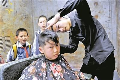 罗福兴在为顾客剪头发。