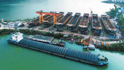 图为重庆市云阳县青龙街道健民村三坝溪船舶建造基地的航拍照片,7艘主体基本完成的新船矗立在库岸边。饶国君摄(人民图片)