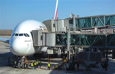 2月7日,一架飞机到达后,首都机场博维公司工作人员操作客梯廊桥与飞机连接后下客。