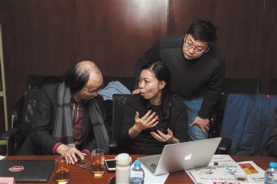 12月16日,2022年冬奥特许商品评审会现场,特许生产商与会徽设计者林存真(中)交流特许商品的改进思路。 扫一扫,上北京2022特许商品官方网店