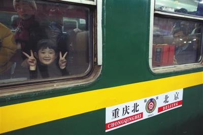 今日零时52分,北京春运首趟临客3603次列车开往重庆北,已经乘车的小朋友隔着车窗招手。新京报记者 王贵彬 摄
