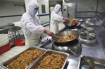 """2月6日,高铁""""后厨""""熟制加工区工作人员在制作干炒牛河。"""