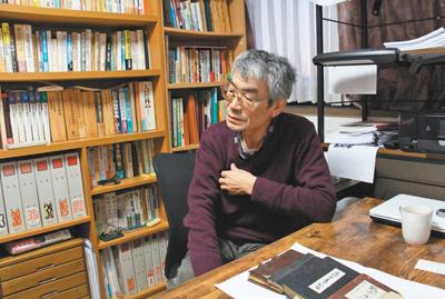小野贤二在书房讲述自己的研究经历。书桌上摆放的是他收集的侵华日军士兵日记。 人民日报记者 刘军国 摄