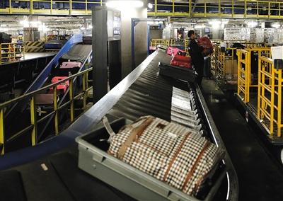 2月7日,首都机场T3,旅客托运的行李通过自动化设备分类后,人工将行李装运到各飞机上。 A04-A05版摄影/新京报记者 陶冉