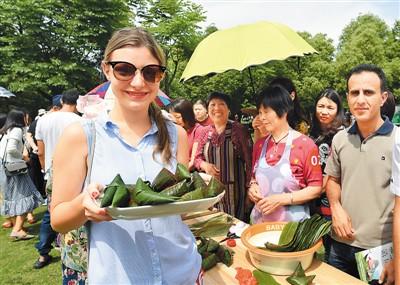 端午节时,外国游客与浙江义乌当地居民一起包粽子。龚献明摄(人民图片)