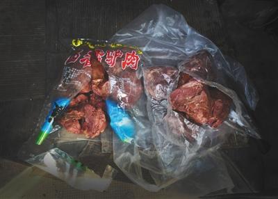 """一名黑作坊老板带了两袋""""驴肉""""给记者看货,左边一袋为冷冻马肉,右边一袋实为猪肉。"""