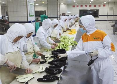 2月6日,北京京铁列车服务有限公司配餐基地,蔬菜加工区工作人员正在切菜。本版摄影/新京报记者 王贵彬