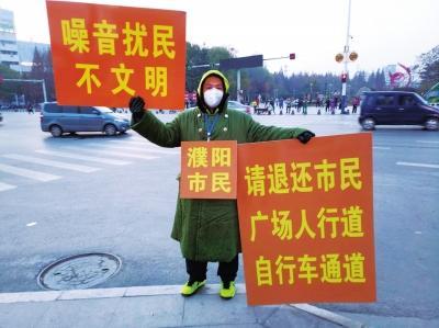 濮阳市民王磊在路这边举牌,广场舞大妈在路那边跳舞。