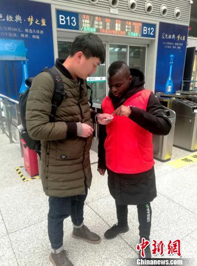 一名喀麦隆留学生在认真回答旅客咨询。 刘鹏 摄