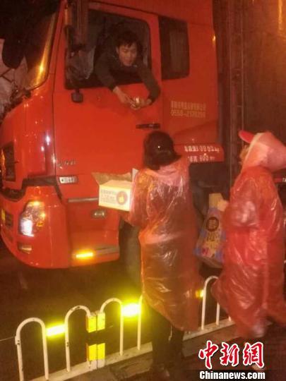 志愿者在雨夜中为滞留旅客服务。官方供图