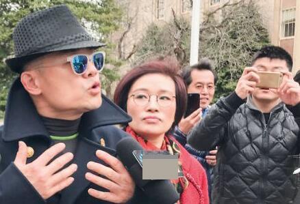 周立波(戴帽者)2017年被控罪后在长岛纳苏郡地区法庭外接受记者访问。(图源:侨报)