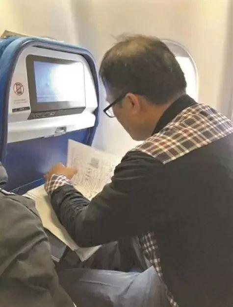 潘老师在飞机上批改试卷